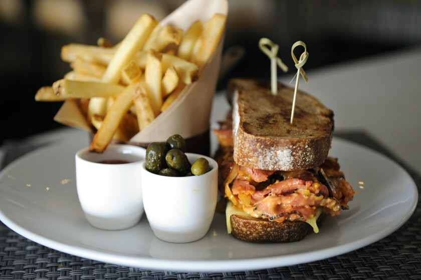 Birch's grilled cheese Reuben made with pastrami, bacon sauerkraut and Russian dressing is served with fries and pickles.