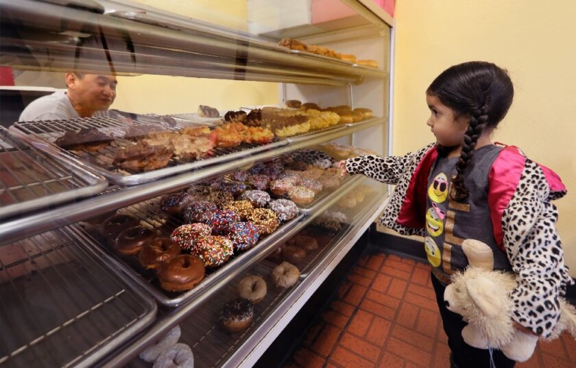 At Chow's Donuts on Friday, 3-year-old Izabelle Castillo points out her doughnut of choice to shop owner Bernard Simieng, at left. The girl was at the shop with her mom, Margie Castillo, a Chow's customer for 15 years. The shop may lose its lease in July.
