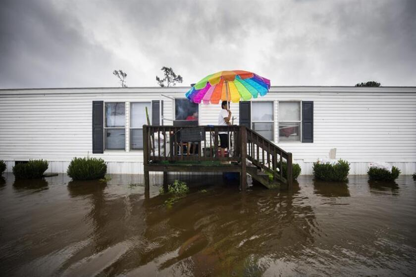 Erick Martinez (C) grills chicken on the porch of his home as floodwaters from Hurricane Florence rise in the Magnolia Mobile Home Park north of Lumberton, North Carolina USA. EFE/EPA