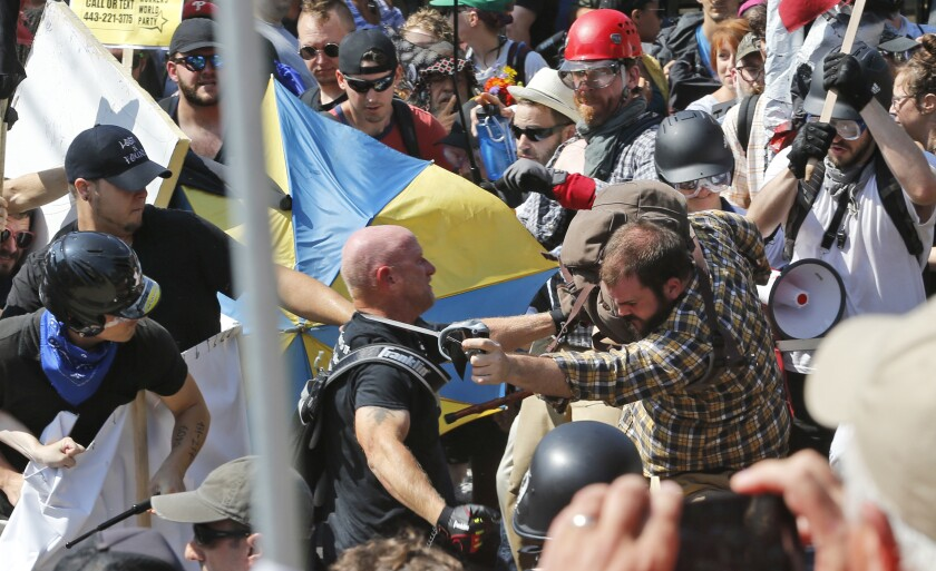 In this Aug. 12, 2017, file photo, white nationalist demonstrators clash with counterprotesters in Charlottesville, Va.