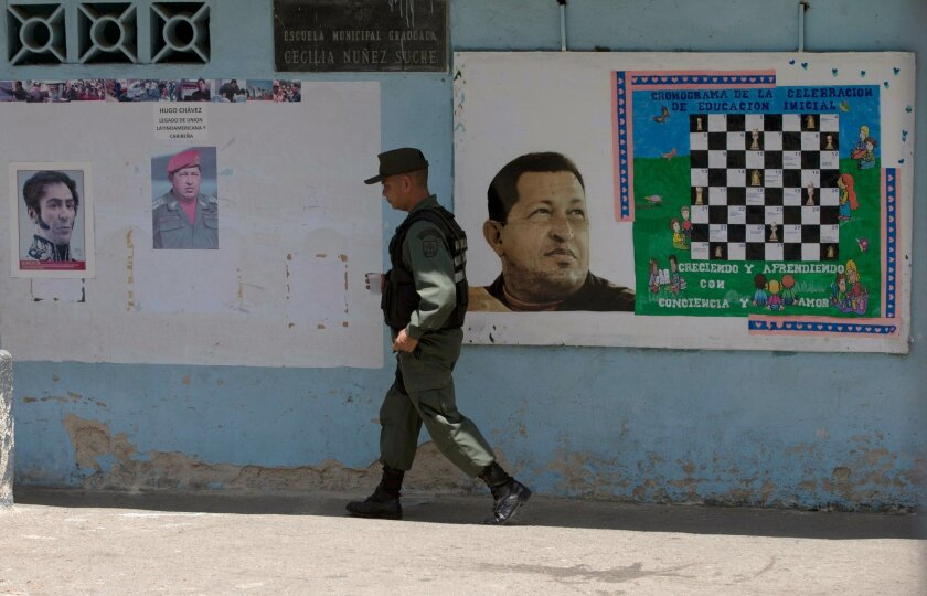 A Bolivarian National Guards officer walks near images of the late Venezuelan President Hugo Chavez and Independence hero Simon Bolivar, left, at a poll station in Caracas, Venezuela, Sunday, May 17, 2015. Venezuelans are voting to select the opposition leaders who will run against the ruling socia