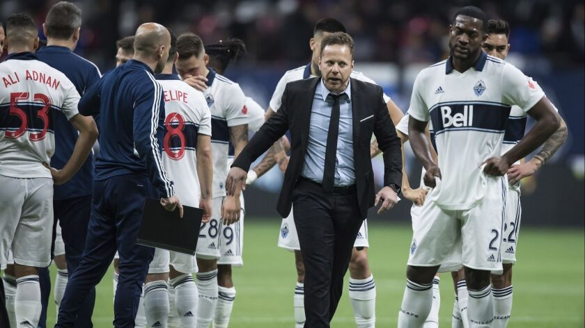 Vancouver Whitecaps coach Marc Dos Santos, second from right, and Doneil Henry, right, leave the fie