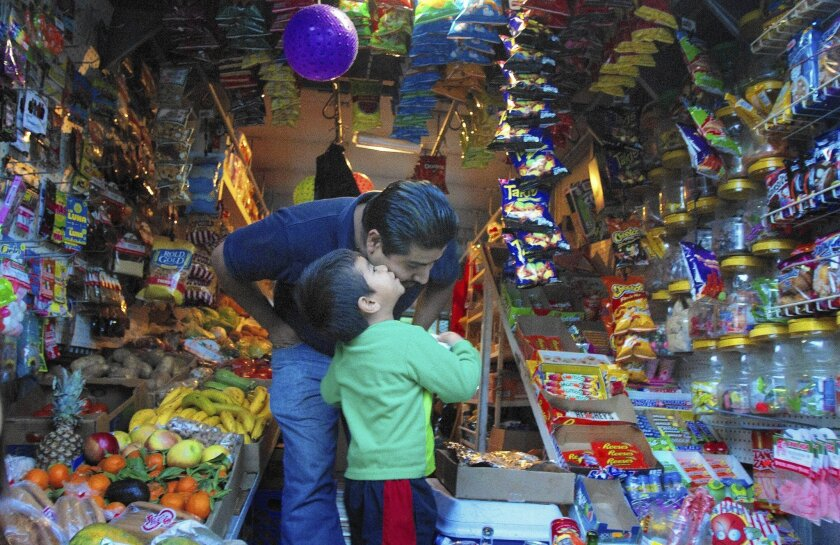 Benjamin Cruz gets a kiss from his son, Jonathan, 4, while driving his produce-store truck in their Pasadena neighborhood. Cruz is one of the few vendors selling produce, snacks and household items out of a roving truck to the Latino neighborhood in Pasadena.