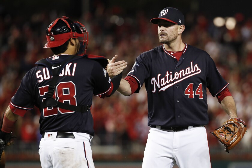 Washington Nationals relief pitcher Daniel Hudson (44) and catcher Kurt Suzuki (28) celebrate the final of Game 4 of a baseball National League Division Series against the Los Angeles Dodgers, Monday, Oct. 7, 2019, in Washington. (AP Photo/Alex Brandon)
