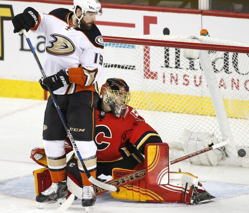 Anaheim Ducks' Patrick Maroon, left, provides a screen in front of Calgary Flames' goalie Jonas Hiller, from Switzerland, as a shot by Ducks' Hampus Lindholm, from Sweden, scores during first period NHL action in Calgary, Alberta, Monday, Feb. 15, 2016. (Larry MacDougal/The Canadian Press via AP) M
