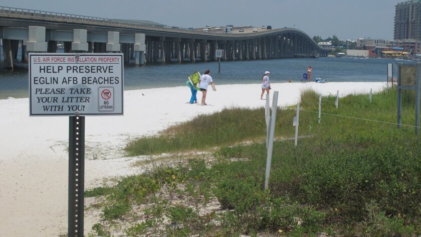 In this July 7, 2014 photo, people look for a place to set up on a shallow beach under a highway bridge in Destin, Fla. The beach is under the controlled of Eglin Air Force Base where it is occasionally used to practice amphibious landings and test high-tech weapons. The public is welcome to use th