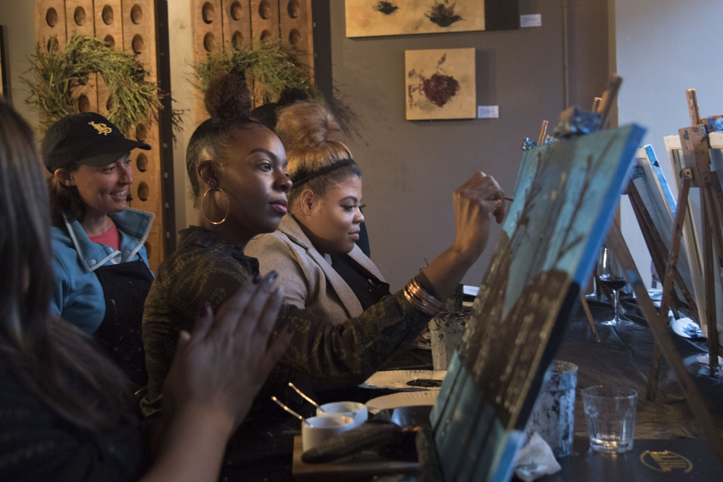 Candice Branch of Corona, center, and Janelle Tarver, right, of Rancho Cucamonga, learn to paint at District Wine with Brushstrokes and Beverages, which partners with area businesses to hold painting classes in Long Beach's East Village.