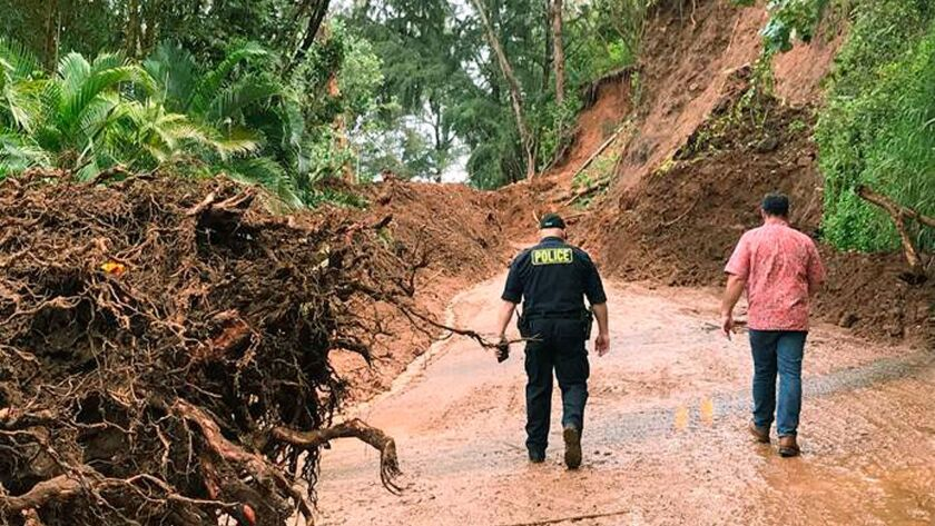 Officials survey damage last Thursday from a recent storm on the island of Kauai that left the area temporarily flooded. Tourism officials tell travelers it's safe to visit popular places such as Hanalei.