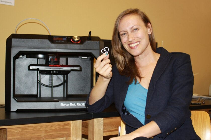 Fab Lab director Katie Rast holds a 3-D printed paperclip made on the MakerBot Replicator printer.