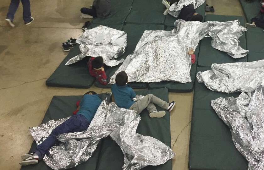 In a photo provided by U.S. Customs and Border Protection shows people who've been taken into custody related to cases of illegal entry into the United States rest in one of the cages at a facility in McAllen, Texas.
