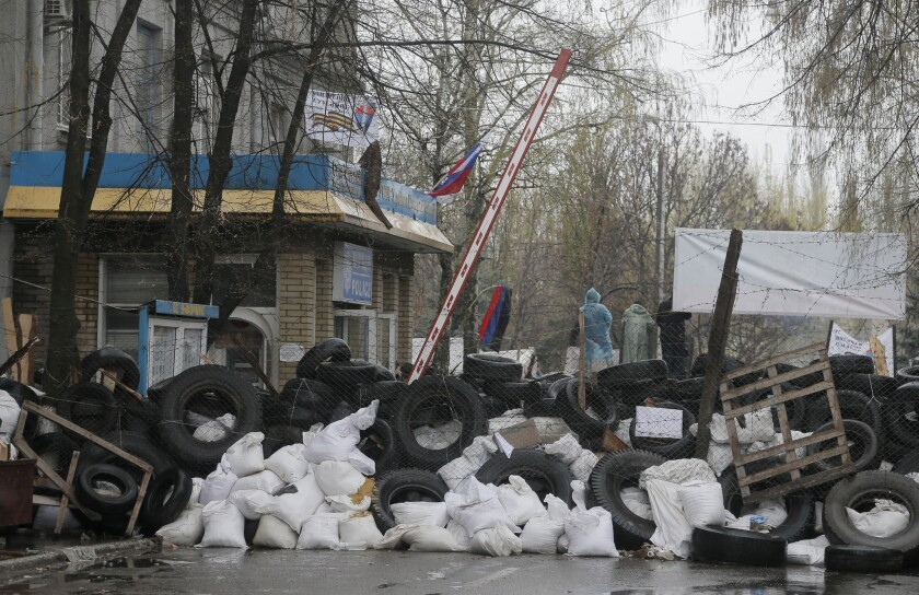 Pro-Russia gunmen stand behind a barrier of tires and trash outside a police station they seized in the eastern Ukraine town of Slavyansk.