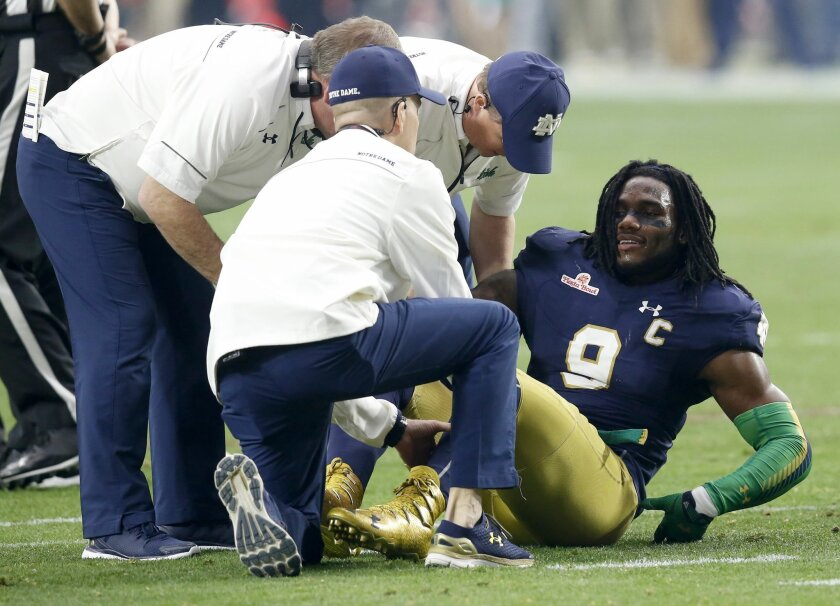 FILE - In this Jan. 1, 2016, file photo, Notre Dame linebacker Jaylon Smith (9) is attended to after a knee injury during the first half of the Fiesta Bowl NCAA college football game against Ohio State in Glendale, Ariz. Smith went early in the second round of the NFL draft to the Dallas Cowboys de