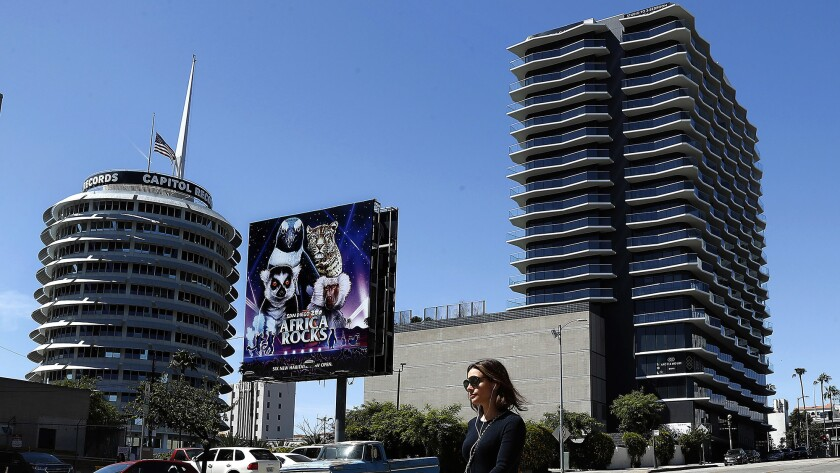 A pedestrian walks along Argyle Ave. in Hollywood with the Capitol Records Building, left, and Argy