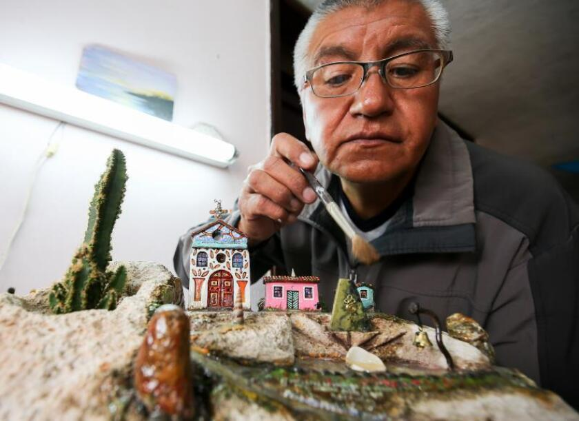 Miniaturist sculptor Jaime Puetate works on one of his artworks on March 21, 2019, in Quito, EPA-EFE/Jose Jacome
