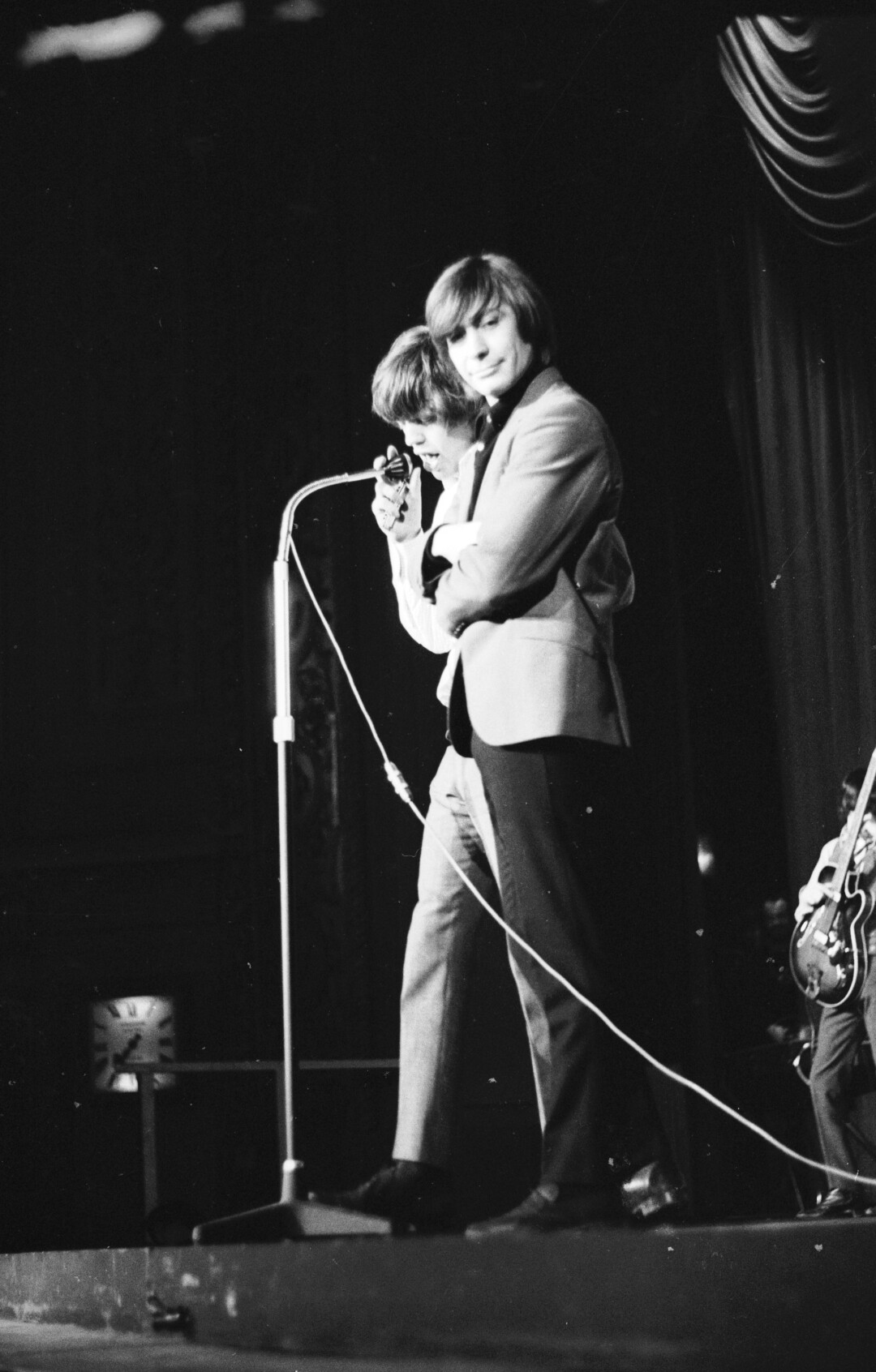 January 1965: Singer Mick Jagger and drummer Charlie Watts stand at a microphone.