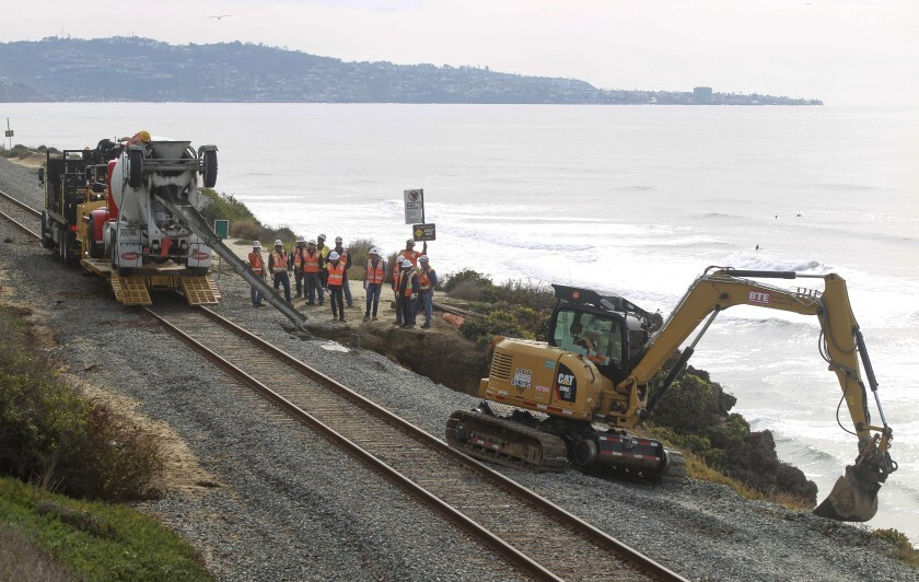 Workers repair the site of a bluff collapse next to the railroad tracks in Del Mar in late November.