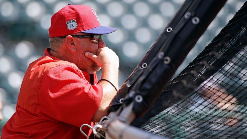 Philadelphia Phillies coach Matt Stairs watches batting practice before a spring training baseball g