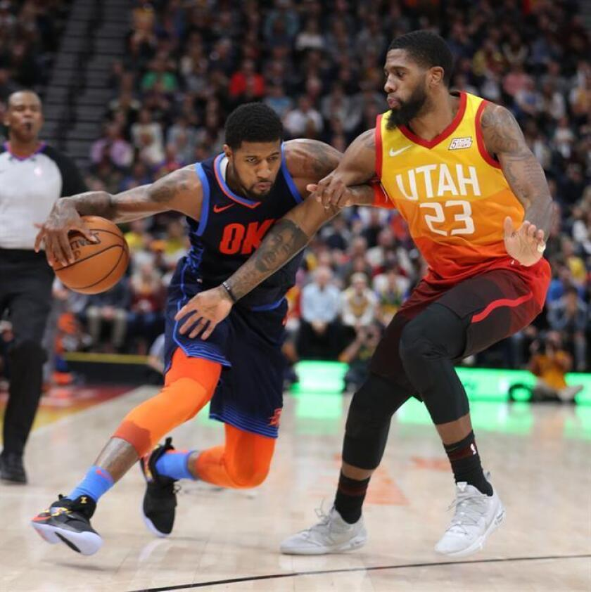 Royce O'Neale (d), de los Jazz de Utah, fue registrado este sábado al intentar superar la marca de Paul George (i), de los Thunder de Oklahoma, durante un partido de la NBA, en el Vivint Smart Home Arena de la ciudad de Salt Lake City (Utah, EE.UU.). EFE