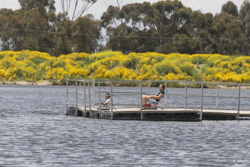 Erin Rose and her 4-year-old son Jaxon practice social distancing as they fish from a pier at the newly reopened Chollas Lake Park in San Diego on April 21.