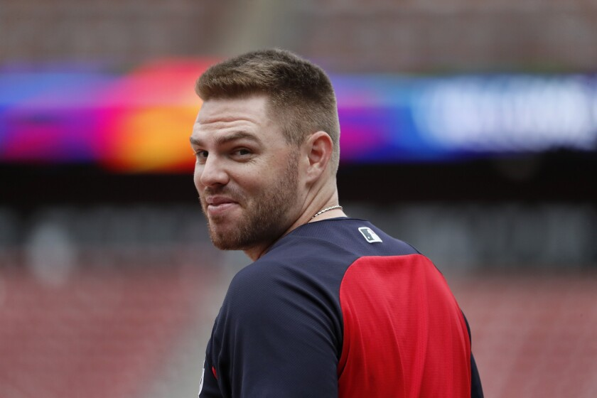 FILE - In this Oct. 5, 2019, file photo, Atlanta Braves' Freddie Freeman looks over his shoulder as he enters the batting cage during a baseball workout in St. Louis. Freeman does not know if he has time to be ready for the Braves' opener at the New York Mets. Following a scary journey in his battle with COVID-19, Freeman knows he is grateful to even have a chance. (AP Photo/Jeff Roberson, File)