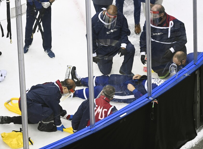Medical staff surround Toronto Maple Leafs defenseman Jake Muzzin as he lays on the ice waiting to be placed on a stretcher as they play against the Columbus Blue Jackets during the third period of an NHL hockey playoff game Tuesday, Aug. 4, 2020 in Toronto. (Nathan Denette/The Canadian Press via AP)