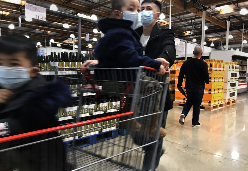 A shopper and his children wear face masks while shopping at Costco on Saturday in Alhambra, Calif.