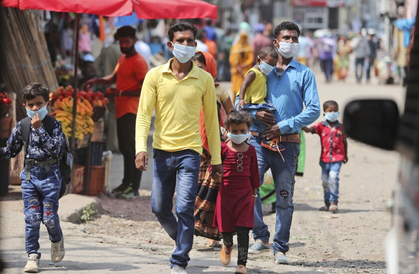 Indians wearing face masks as a precaution against the coronavirus walk at a bus station in Jammu, India, Friday, Sept. 11, 2020. By early May, 6.4 million people in India were likely infected by the coronavirus, said a study released Thursday, Sept. 10, by Indian scientists from the Indian Council of Medical Research, India's apex medical research body and published in their in-house medical journal. At the time, India had detected around 35,000 cases and over a thousand deaths. But the results of India's first nationwide study of prevailing infections in the country found that for every confirmed case that detected in May, authorities were missing between 82 and 130 infections. The study tested 28,000 people for proteins produced in response to the virus in the villages and towns across 70 districts in 21 Indian states between May 11 to June 14. (AP Photo/Channi Anand)