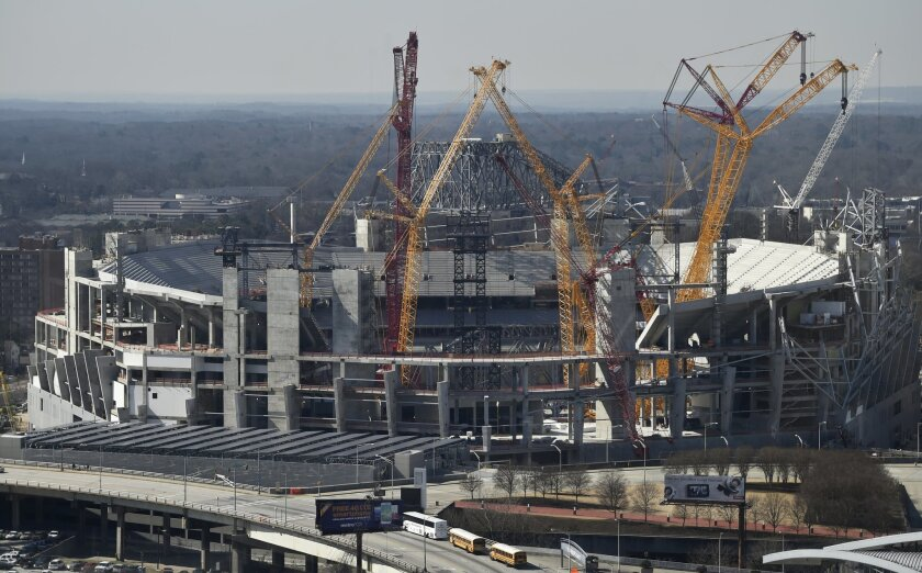 Workers construct the Mercedes Benz Stadium, the future home of the Atlanta Falcons, Thursday, Feb. 11, 2016, in Atlanta. The Falcons say their first year of PSL sales for their new Mercedes Benz Stadium has gone well. Even so, the idea of paying extra for the right to buy season tickets hasn't bee