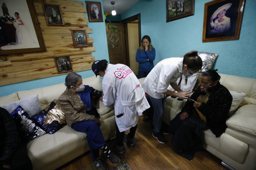 La doctora Tania Díaz Bravo, izquierda, revisa los signos vitales de Esther Canales Cruz, de 78 años