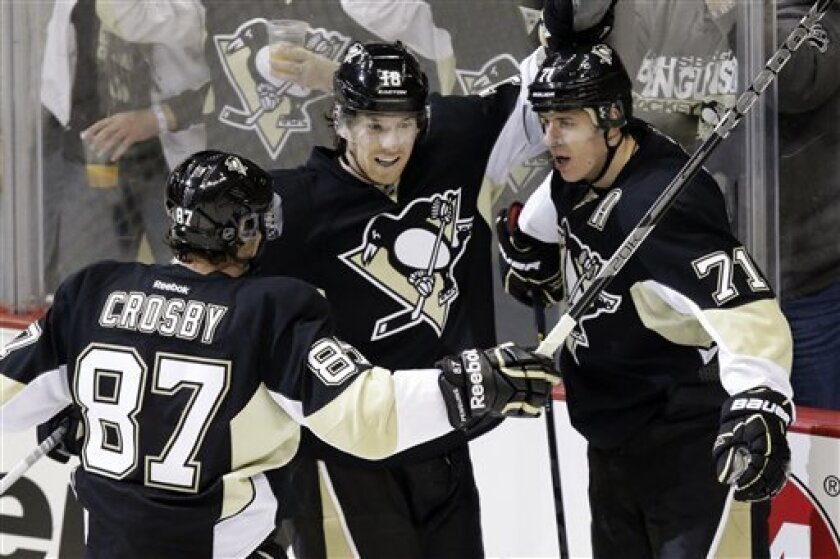 Pittsburgh Penguins center Evgeni Malkin (71) celebrates with left wing James Neal (18) and center Sidney Crosby (87) after scoring in the first period of an NHL hockey game against the Philadelphia Flyers in Pittsburgh, Wednesday, Feb. 20, 2013. (AP Photo/Gene J. Puskar)