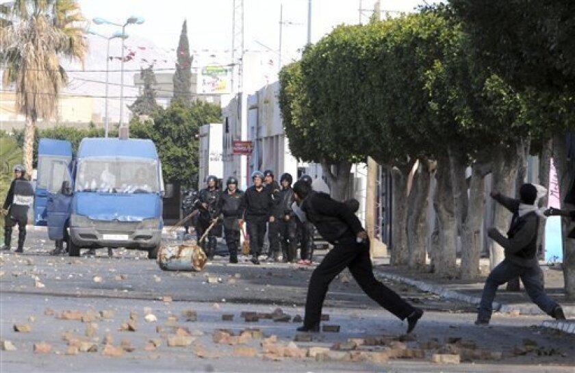 Demonstrators throw stones at police officers in Sidi Bouzid, Tunisia, Monday Jan. 10, 2011. Tunisia's Interior Ministry said Monday that 14 people were killed in weekend rioting in three towns in the deadliest episodes in more than three weeks of unusual unrest in this popular tourist destination. Union officials around Tunisia have provided their own death counts, higher than the official number. (AP Photo)