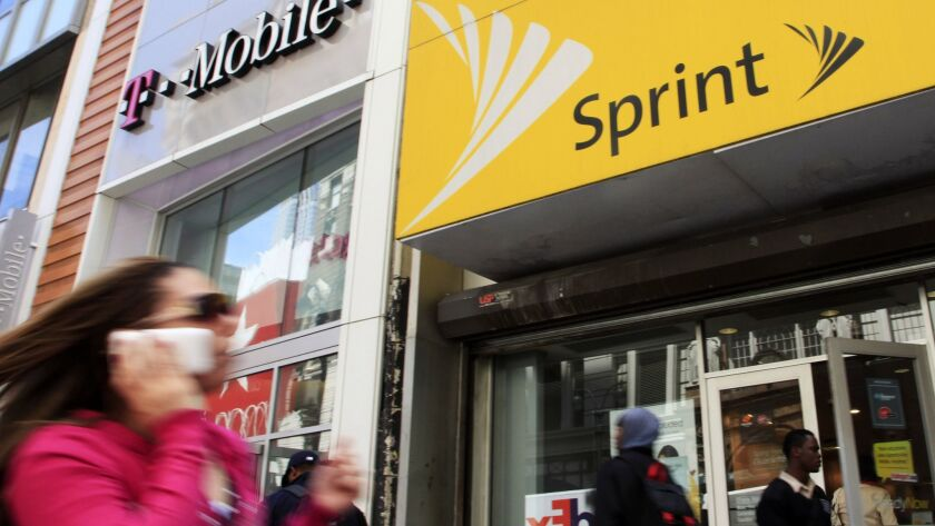 A woman using a cellphone walks past T-Mobile and Sprint stores in New York in 2010.
