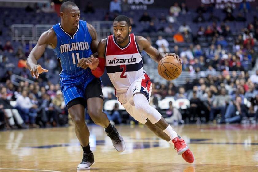 El jugador de Magic Bismack Biyombo (i) intenta bloquear a John Wall (d) de Wizards, durante un partido entre Magic y Wizards por la NBA en el Verizon Center de Washington (DC, EE.UU.). EFE