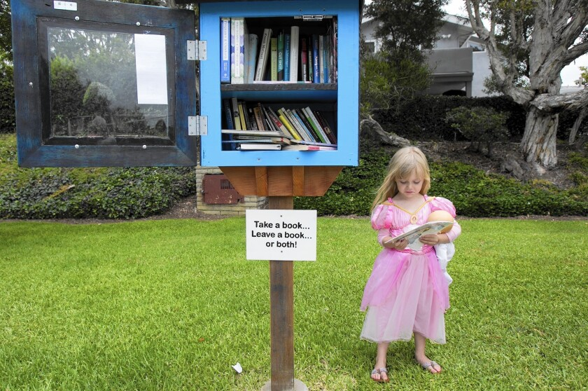 Elle Gamble looks at a book she picked out at the Little Free Library at the Blue Heron Park in Newport Beach on Tuesday.
