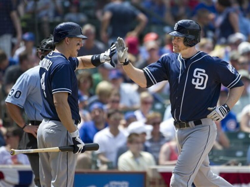 San Diego Padres' Nick Hundley, left, high-fives teammate Chase Headley after Headley hit a solo home run during the fourth inning of a baseball game against the Chicago Cubs, Monday, May 28, 2012 in Chicago.  (AP Photo/Brian Kersey)