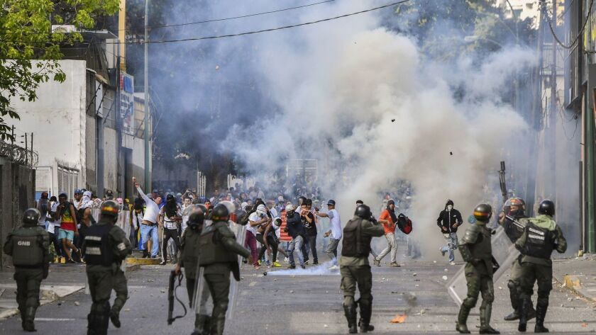 Riot police clash with opposition demonstrators during a protest against the government of President Nicolas Maduro.