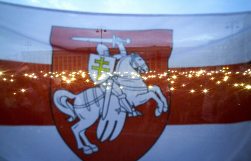 FILE In this file photo taken on Wednesday, Aug. 26, 2020, Belarusian opposition supporters seen through an old Belarusian national flag, as they light their smartphones as they gather at Independence Square in Minsk, Belarus. Protests against President Alexander Lukashenko that gripped Belarus for months seem quelled by Winter's cold and harsh police action, but opposition forces are preparing to turn up the heat in the spring and observers say Lukashenko doesn't have a clear strategy to overcome new unrest. (AP Photo/Sergei Grits, File)