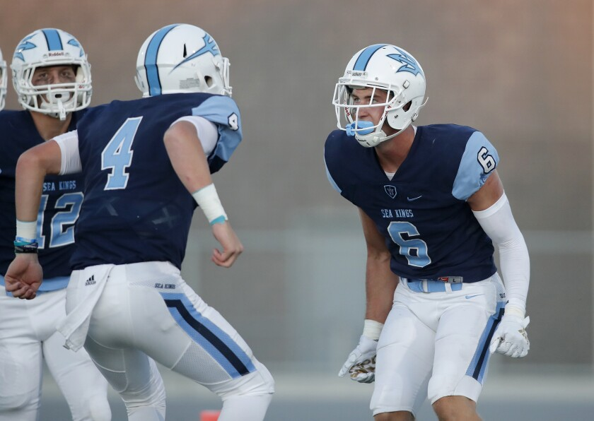 Quarterback Ethan Garbers (4) celebrates with John Humphreys (6) after throwing one of two first-half touchdowns to Humphreys in a season opener against Downey on Friday at Newport Harbor High.