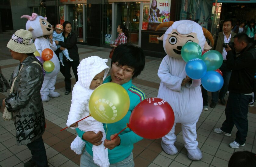 """In this photo taken Sunday, Oct. 2, 2011, Chinese women and children gather near mascots of characters from the cartoon """"Pleasant Goat and Big Big Wolf"""" on a street in Beijing, China. A Chinese court has ruled the producer of the hit kids cartoon was partly to blame for the injuries suffered by two"""