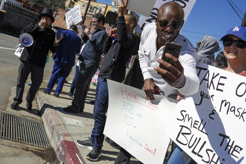 Los Angeles, CA - January 30: Siaka Massaquoi, right, listed on IMDb as an actor, was one of the protesters who protested the vaccine clinic at Dodger Stadium on Saturday, Jan. 30, 2021 in Los Angeles, CA.(Irfan Khan / Los Angeles Times)