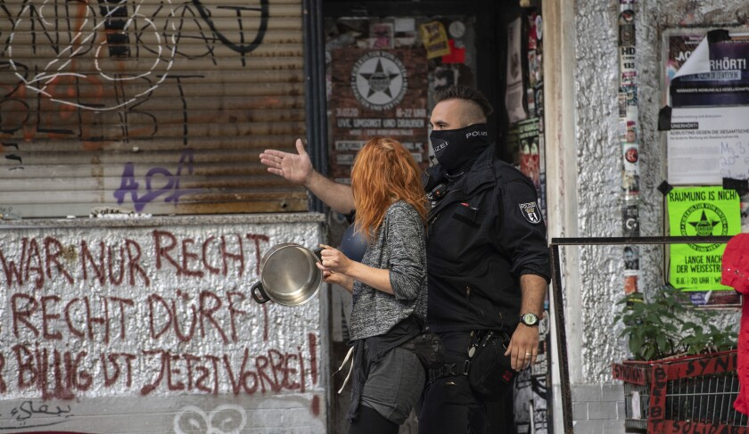 A police officer leads a demonstrator out of the cordoned-off area at the Weisestrasse in Berlin, Germany, where the bar 'Syndicate' is being evacuated on Friday, Aug. 7, 2020. Protesters have erected barricades and set several fires in a bid to stop Berlin police from evicting a left-wing bar that has been the focus of a campaign against gentrification. (Paul Zinken//dpa via AP)