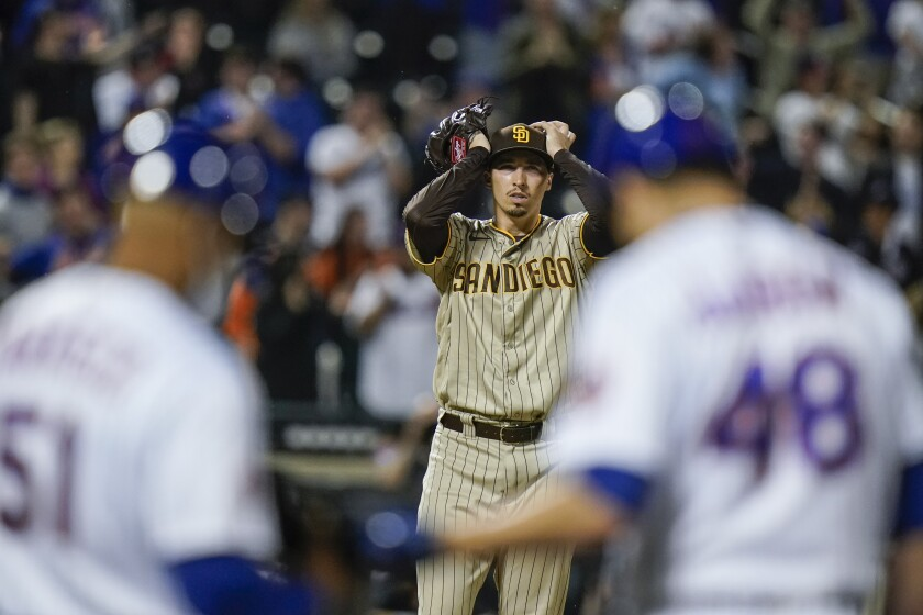 Padres pitcher Blake Snell, center, reacts after the New York Mets' Jacob deGrom hit a two-run single