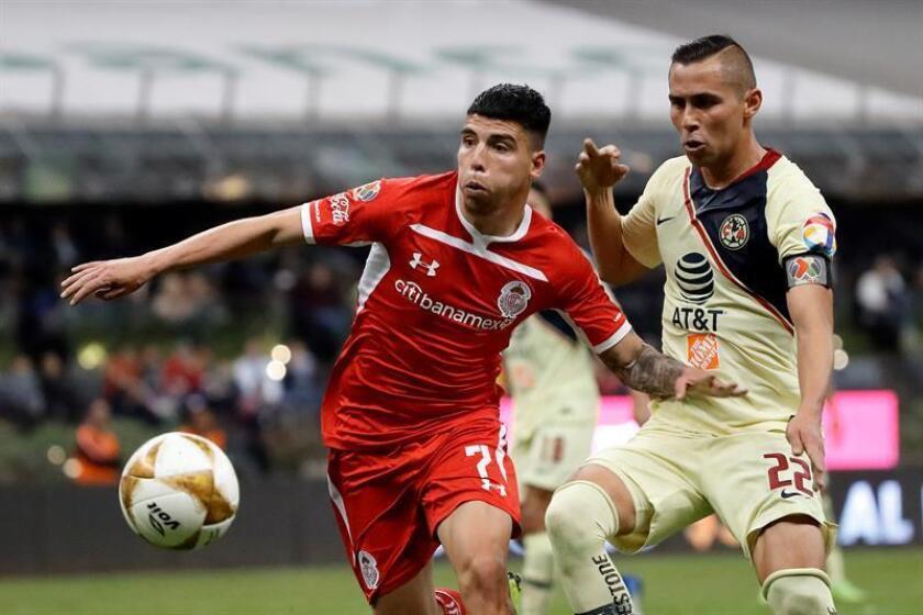 El jugador de América Paul Aguilar (d) disputa el balón con Luis Mendoza (i) de Toluca. EFE/Archivo