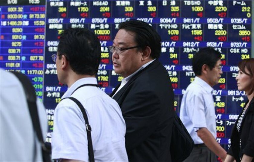 People stroll by an electronic stock indicator in Tokyo, Monday, Sept. 6, 2010. Japan's benchmark Nikkei 225 stock index climbed 2 percent, or 179.95 points, to 9,294.61. (AP Photo/Shizuo Kambayashi)