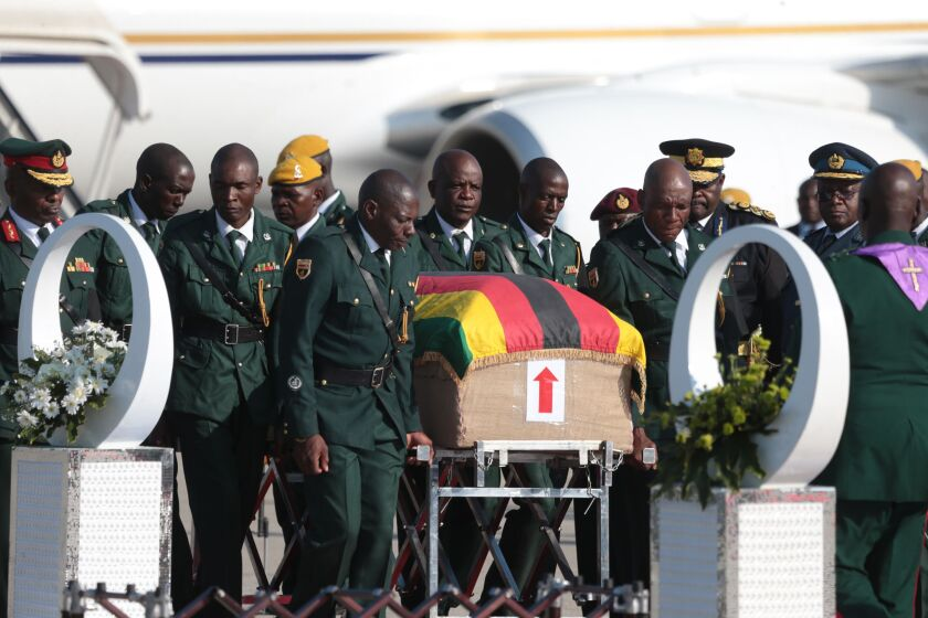 Members of the Presidential Guard stand beside the coffin of late former President Robert Mugabe upon its arrival in Harare, Zimbabwe, on Wednesday.