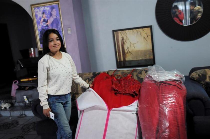 La joven mexicana Rubí posa junto a su vestido de quinceañera hoy, miércoles 14 de diciembre de 2016, en su casa de La Joya del estado de San Luis Potosí (México). EFE/STR