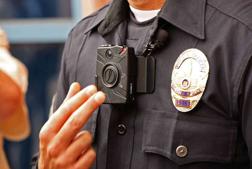 A police officer demonstrates how to turn on a new LAPD body camera during a press conference on Sept. 4, 2015.