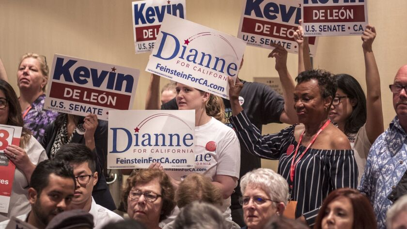 Supporters of Kevin de Leon and Dianne Feinstein hold signs during a meeting of the women's caucus at the Marriott Hotel in downtown Oakland.