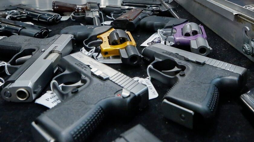 Handguns, many of them semiautomatic, are displayed on a vendor's table at a gun show in Albany, N.Y., in 2013.