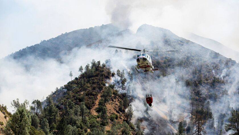 A helicopter gathers water from the Merced River to fight the Ferguson Fire along steep terrain behi